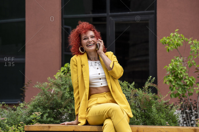 Businesswoman with curly hair- wearing yellow suit- talking on the phone