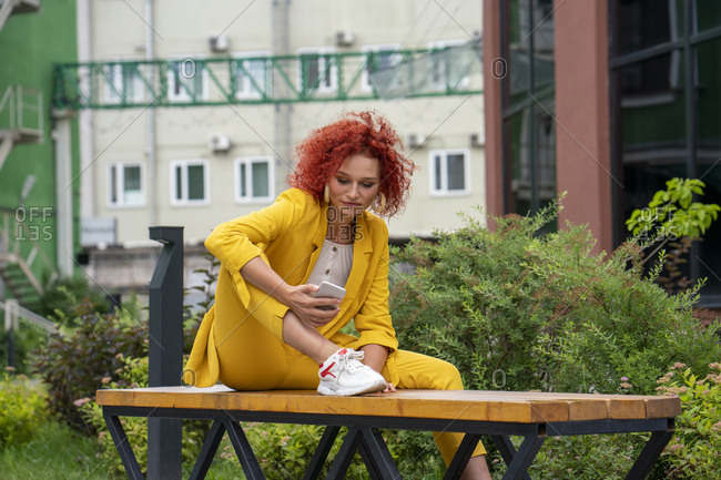 Businesswoman with curly hair- wearing yellow suit- using smartphone