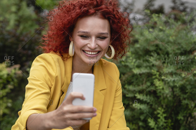 Businesswoman with curly hair- wearing yellow suit- taking smartphone selfie