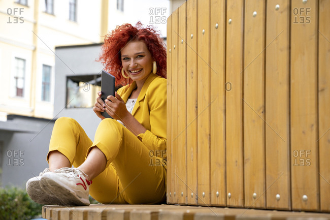 Young woman with curly hair and yellow suit- sitting on bench- using digital tablet