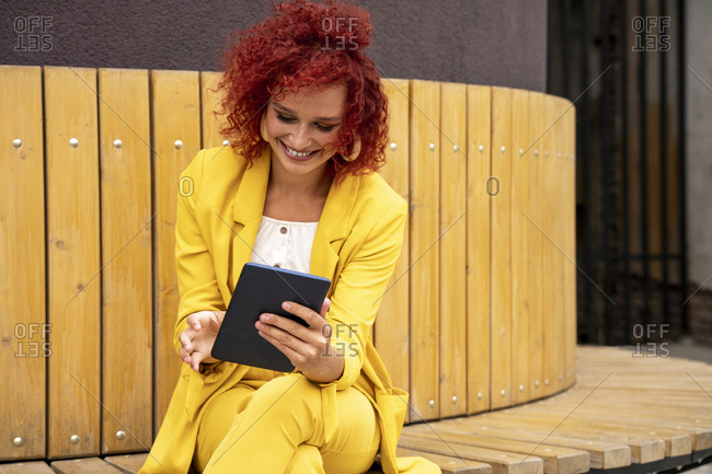 Young woman with curly hair and yellow suit having a video chat on digital tablet