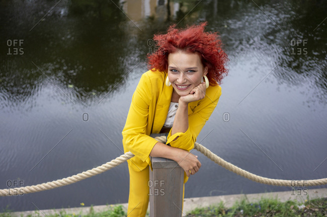 Young woman with curly hair and yellow suit standing by river leaning on pole
