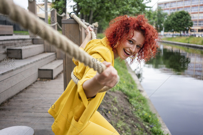 Young woman with curly hair and yellow suit sitting by the riverside- holding onto rope