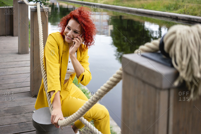 Young woman with curly hair and yellow suit sitting by the riverside- talking on the phone