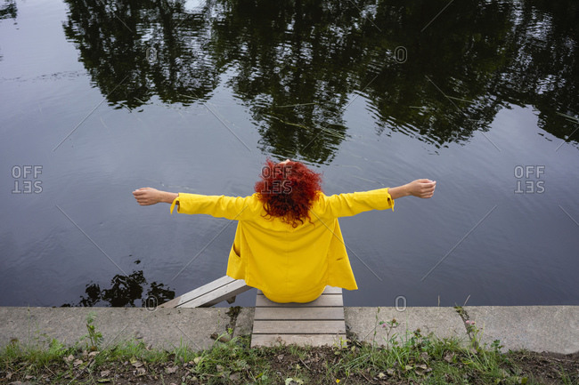 Young woman with curly hair and yellow suit sitting by the riverside with arms outstretched