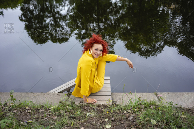 Young woman with curly hair and yellow suit sitting by the riverside
