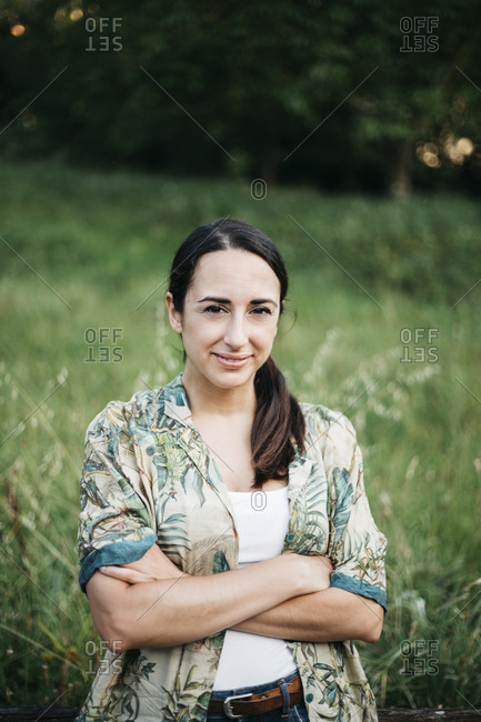 Smiling woman with arms crossed standing in public park