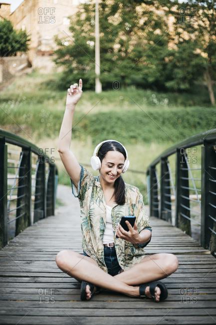 Happy woman doing dance moves while listening music through headphones on footbridge