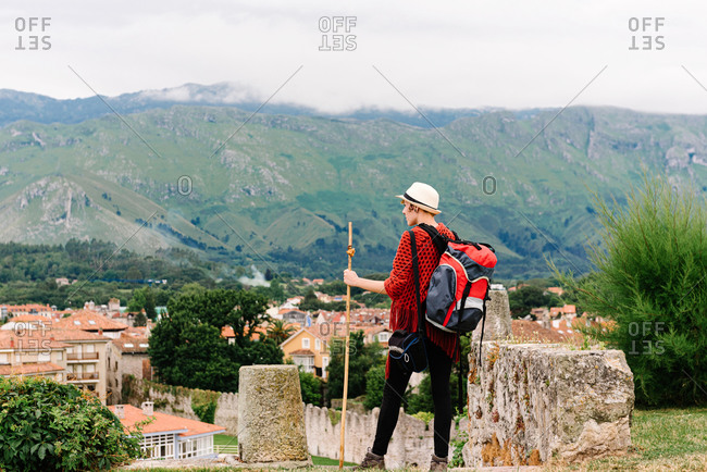 Back view of unrecognizable female backpacker with stick standing on hill and exploring old town located against mountains during pilgrimage trip through Spain