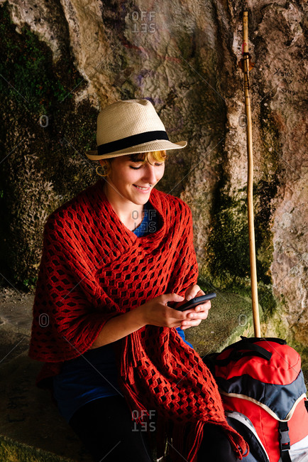 Happy young ethnic female hiker in stylish outfit with backpack and hiking stick sitting in rocky cave using on smartphone while relaxing during trekking in Spain