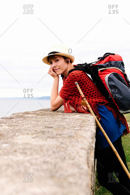 Side view of amazed young female pilgrim with backpack and trekking stick standing on sea coast looking at camera while enjoying trip along Camino de Santiago in Spain