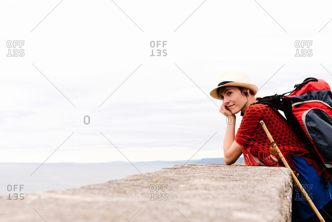 Side view of amazed young female pilgrim with backpack and trekking stick standing on sea coast looking away  while enjoying trip along Camino de Santiago in Spain