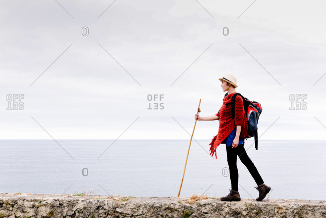 Full body side view of female hiker with backpack and trekking stick standing on stone cliff border against gray cloudy sky and enjoying freedom during pilgrimage through Spain