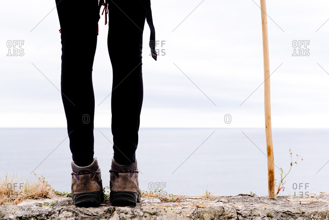 Cropped unrecognizable female hiker with trekking stick standing on stone border against gray cloudy sky and enjoying freedom during pilgrimage through Spain