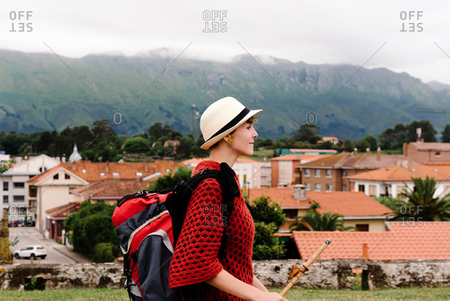Side view of happy female backpacker with stick standing on hill and exploring old town located against mountains during pilgrimage trip through Spain