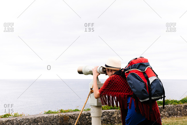 Back view of unrecognizable female traveler in stylish outfit with backpack looking through binocular telescope and admiring sea during pilgrimage trip through Spain
