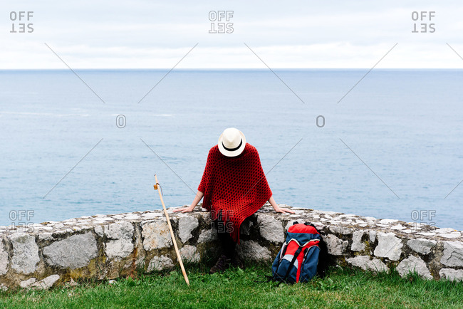 Happy young female backpacker in stylish clothes sitting on stone border against sea bay and looking down while resting during Camino de Santiago route in Spain