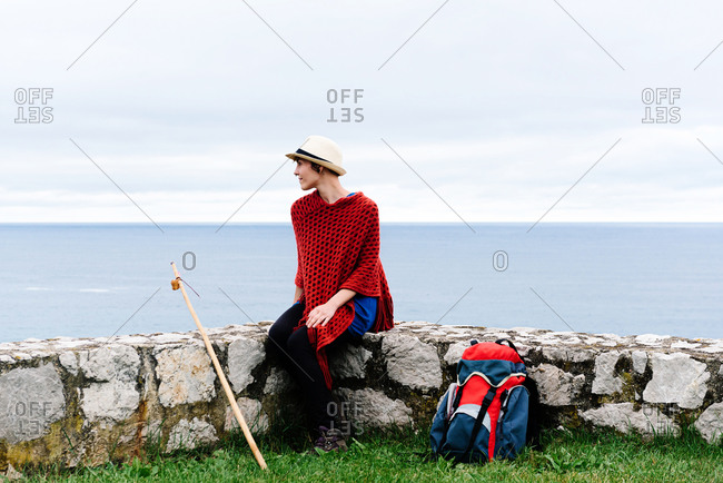 Happy young female backpacker in stylish clothes sitting on stone border against sea bay and looking away while resting during Camino de Santiago route in Spain