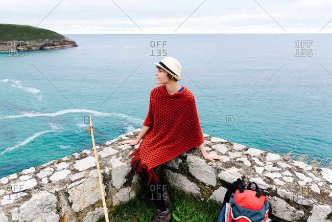 From above female backpacker in stylish clothes sitting on stone border against sea bay and looking away while resting during Camino de Santiago route in Spain