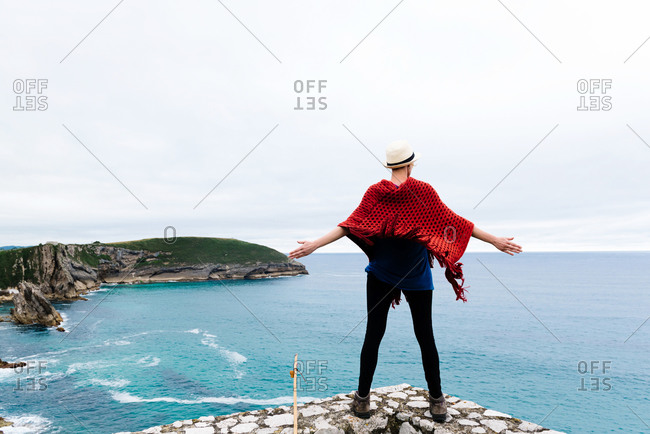 Full body back view of unrecognizable female hiker with backpack and trekking stick standing with arms raised on stone border against gray cloudy sky and enjoying freedom during pilgrimage through Spain