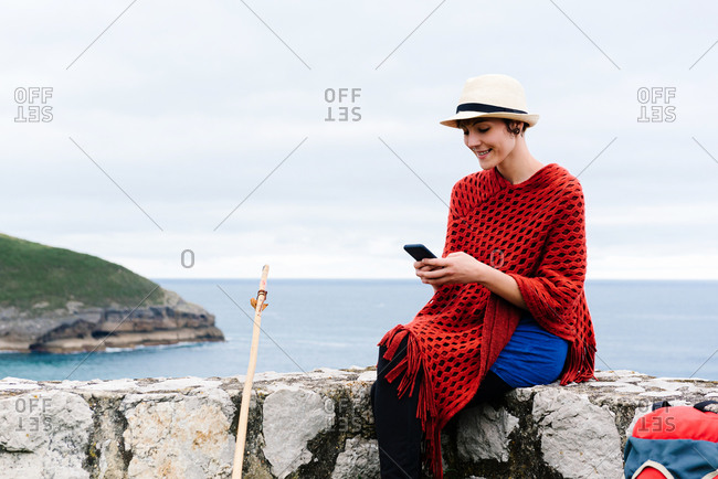 Young female backpacker with trekking stick sitting on stone border near sea and browsing smartphone while resting and checking route during pilgrimage through Spain