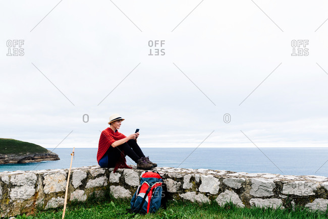 Full length side view of young female backpacker with trekking stick sitting on stone border near sea and browsing smartphone while resting and checking route during pilgrimage through Spain