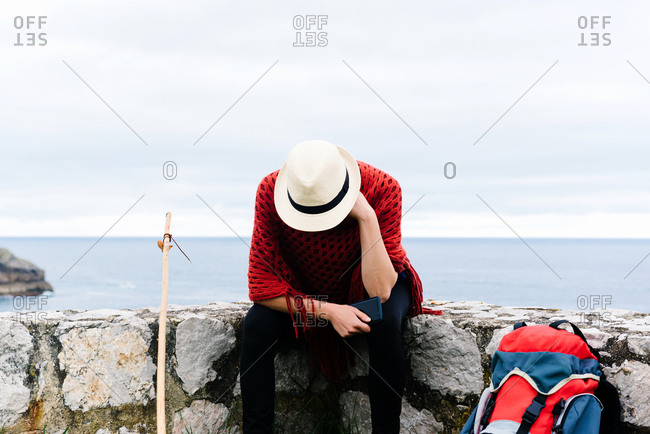 Unrecognizable sad lost female backpacker with trekking stick sitting on stone border near sea and browsing smartphone while resting and checking route during pilgrimage through Spain