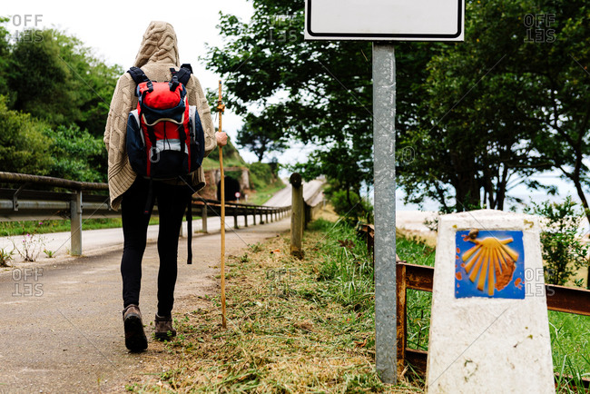Back view of lonely unrecognizable hiker with backpack and trekking stick walking on path near signpost with scallop shell symbol of Camino de Santiago in Spain