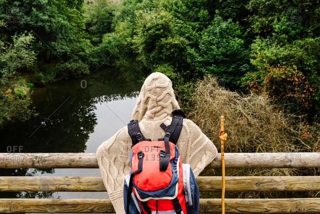 Back view of anonymous backpacker in warm knitted wear with hood leaning on wooden railing against small pond surrounded with green trees while resting during hiking in Spain