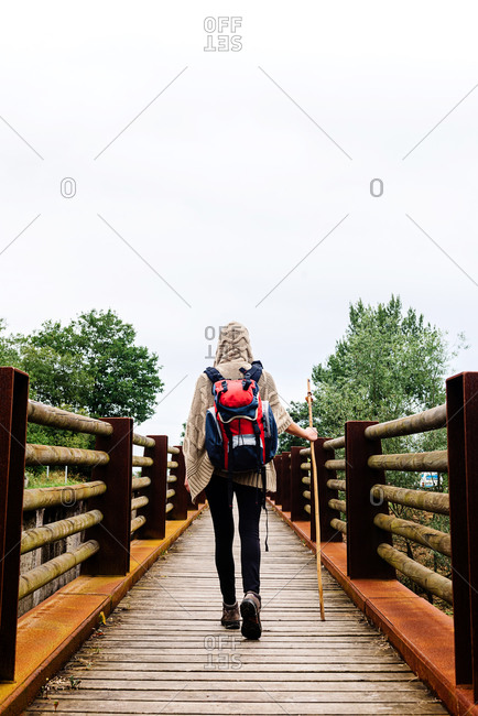 Full body back view of unrecognizable traveler with backpack and trekking stick walking alone on wooden footbridge during hiking through Spain