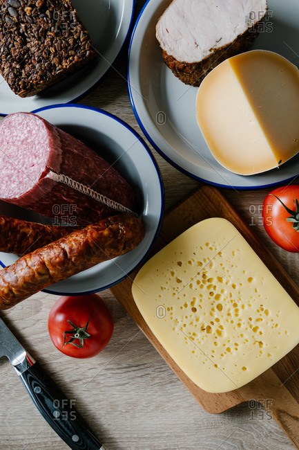 Top view of delicious cheese and salami arranged on table with ripe tomatoes and wholegrain bread in kitchen