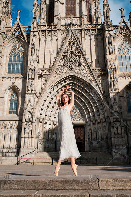 Full body low angle of elegant young ballerina in dress standing on tiptoe while performing sensual dance against aged stone cathedral