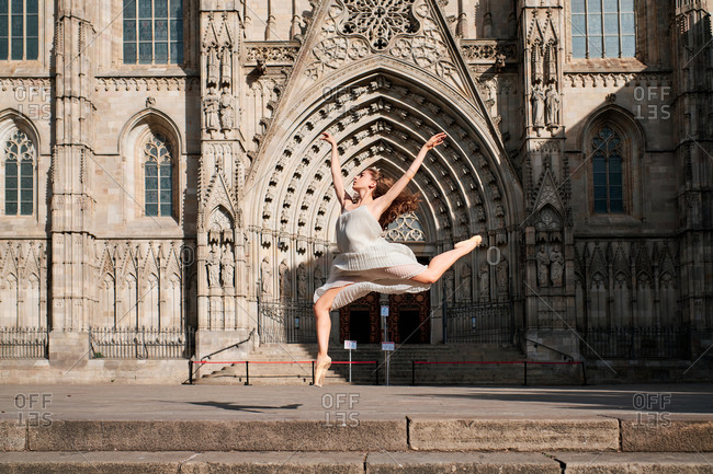 Full body of young female ballet dancer performing sensual dance moves and jumping with arms raised against ornamental stone building with Gothic architecture