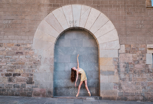 Full body of graceful young female dancer standing in ballet pose against weathered brick wall with arched ornament