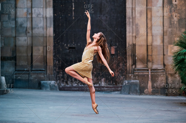 Full body of graceful young female dancer in pointe shoes performing elegant dance with arm raised on narrow paved passage against aged stone building