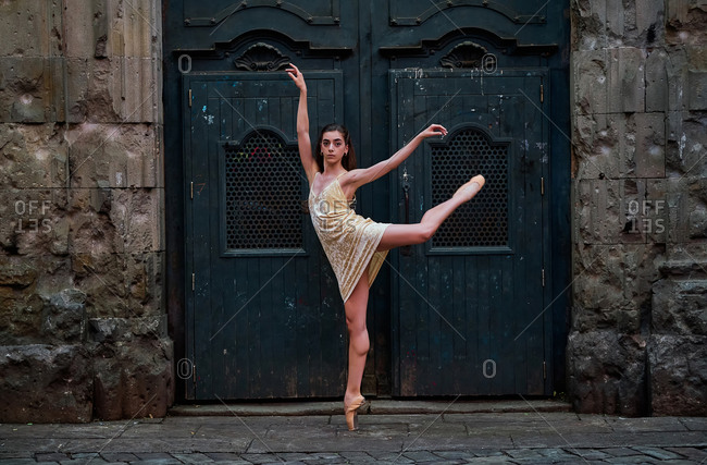 Full body side view of slim young ballerina in dress and pointe shoes performing graceful ballet pose against weathered door of aged stone building on street of old city