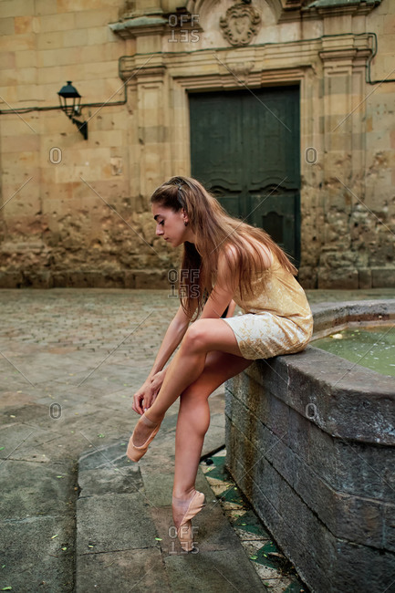 Full body side view of young female dancer putting on pointe shoes while sitting near weathered stone building and preparing for rehearsal on city street