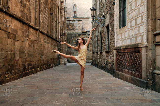 Full body of talented young female ballet dancer in dress and pointe shoes performing dance movement with leg outstretched on narrow paved passage between old stone buildings