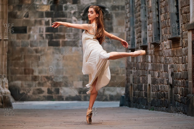 Full body side view of slim young ballerina in dress and pointe shoes performing graceful ballet pose against weathered wall of aged stone building on street of old city