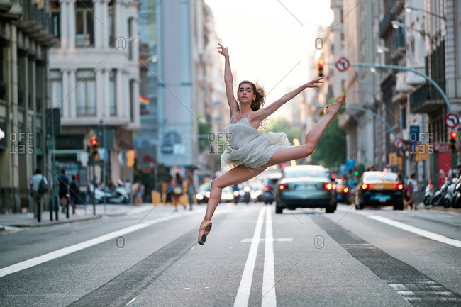 Full body side view of young slim female dancer in pointe shoes jumping and performing split over asphalt road on modern city street with cars and buildings in background