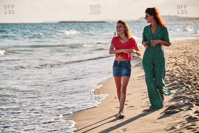 Full body stylish adult woman in elegant outfit and teen daughter talking and laughing while strolling together on sandy beach near waving sea during summer day