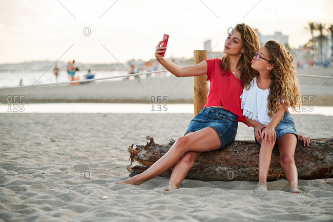 Full body happy teen girl and younger sister with long curly hair taking selfie with smartphone while sitting together on sandy beach in summer evening