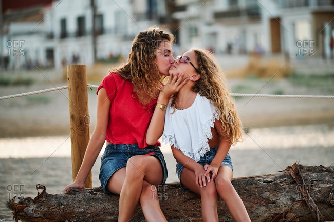 Happy teen girl kissing younger sister while sitting together on wooden log at seaside and enjoying summer holidays together