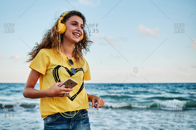 Low angle of optimistic adolescent female in yellow shirt listening to music with smartphone and headphones while resting near waving sea during summer holidays