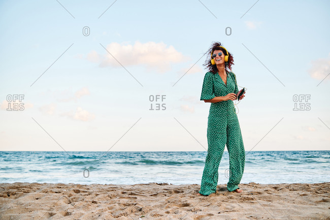 Full body side view of carefree female in stylish outfit with headphones listening music on smartphone while standing on sandy beach near sea in summer day