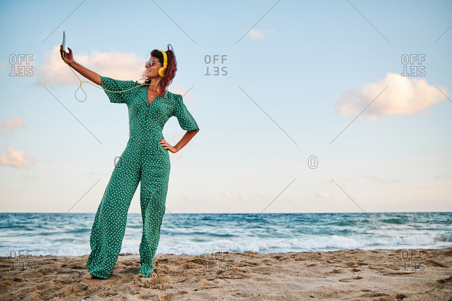 Full body side view of carefree female in stylish outfit with headphones raising hand and taking selfie on smartphone while standing on sandy beach near sea in summer day