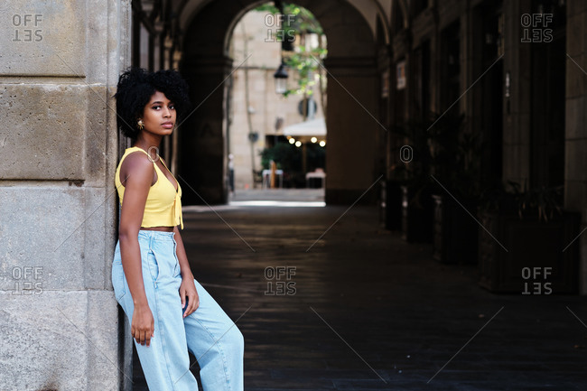 Side view of stylish millennial African American female in casual yellow top and trendy jeans leaning back on stone wall of old building while standing in arched passage on city street