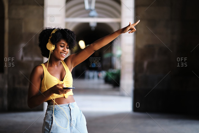 Optimistic young African American female in casual outfit with smartphone and headphones standing on street and enjoying music in summer day