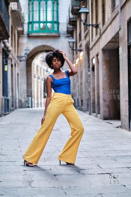 Full body of young slim African American female with curly hair dressed in stylish yellow pants and blue top standing on narrow paved street in old city district