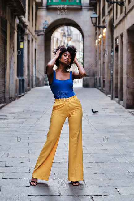 Full body of young slim African American female with curly hair dressed in stylish yellow pants and blue top standing on narrow paved street in old city district touching hair with eyes closed